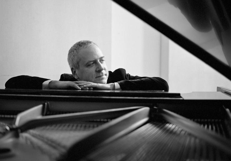 Jeremy Denk sitting at piano landscape B&W