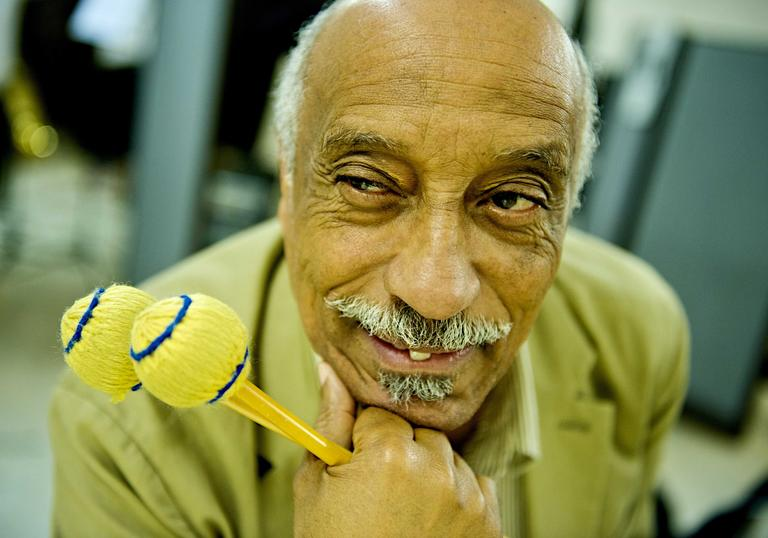 Mulatu Astatke poses with a flamboyant drum stick
