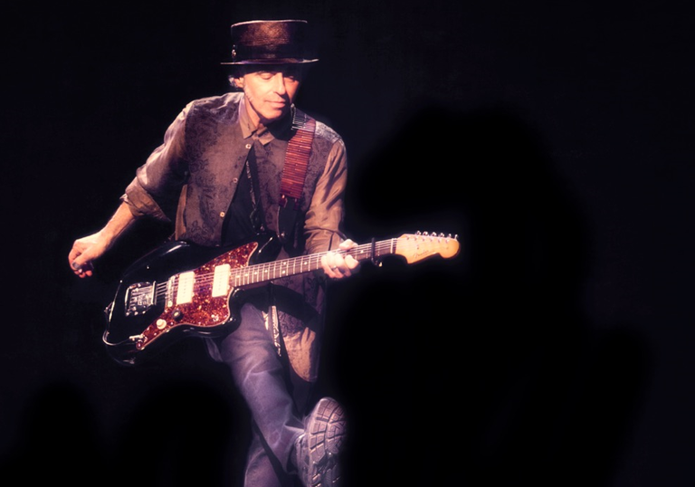 Nils Lofgren pulling over the impressive feat of kicking and playing guitar simultaneously