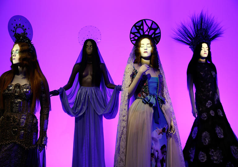 Installation image of Gaultier exhibition with pink background and four mannequins in gowns