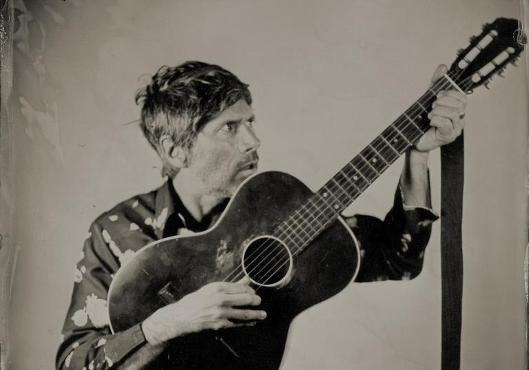 Gruff Rhys with an acoustic guitar