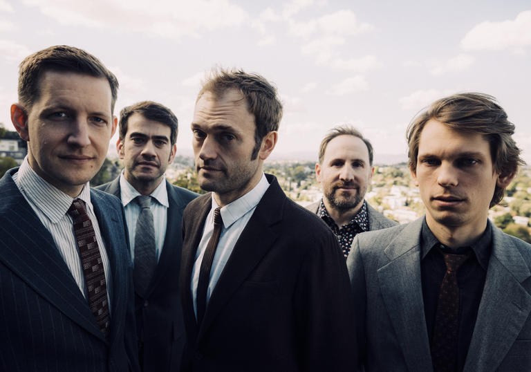 Punch Brothers in suits standing in a field