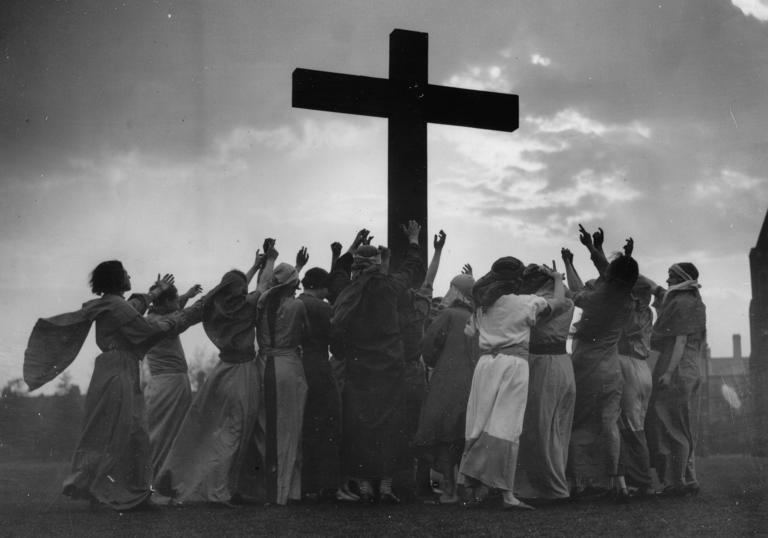 Group of people surrounding a cross