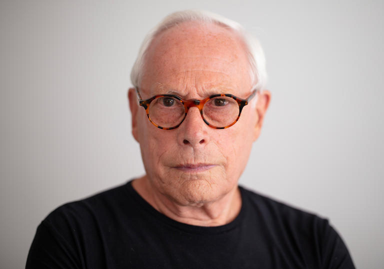 Dieter Rams is wearing a pair of tortoise shell spectacles and a black t-shirt