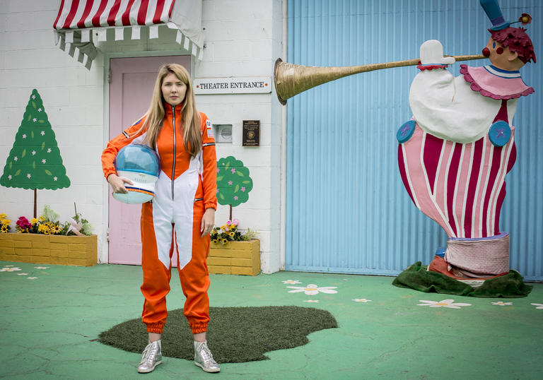 Beatie Wolfe wearing an orange space suit and holding a helmet