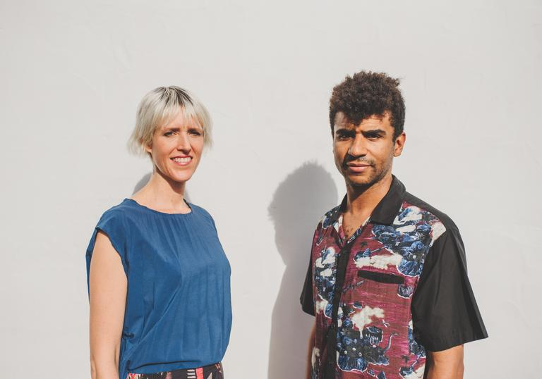 Kate Simko and Jamie Jones smile awkwardly in front of an off-white wall