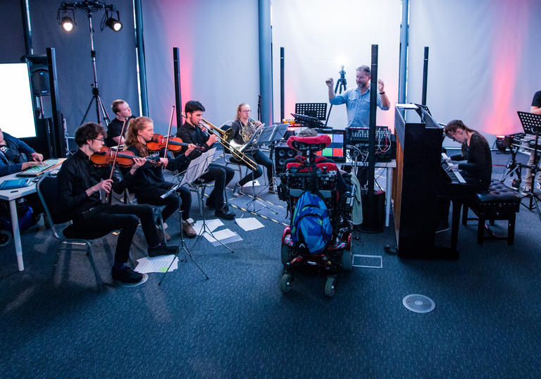 Young musicians who are disabled and able bodied play a selection of instruments as part of the National open Youth Orchestra