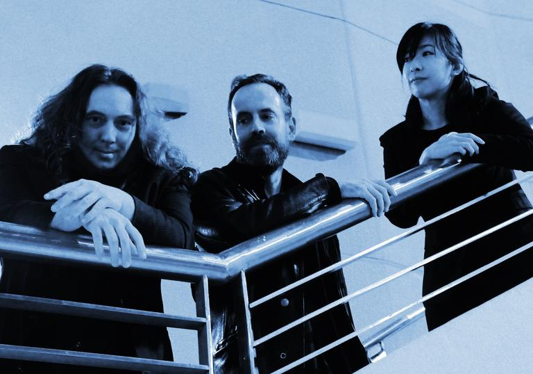 Tangerine Dream are photographed in a dreamy blue filter on what appears to be the upper deck of a small commercial ferry