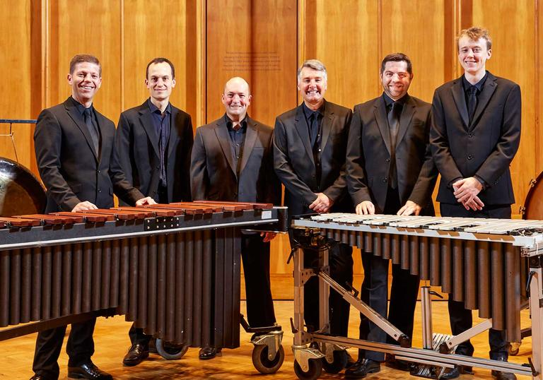 The LSO Percussion Ensemble stands behind orchestral percussion instruments