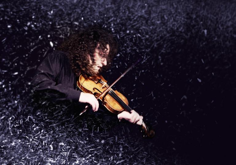 Martin Hayes playing the fiddle surrounded by a dust effect