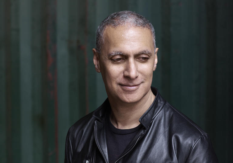 Picture of Nitin Sawhney looking down in a black leather jacket