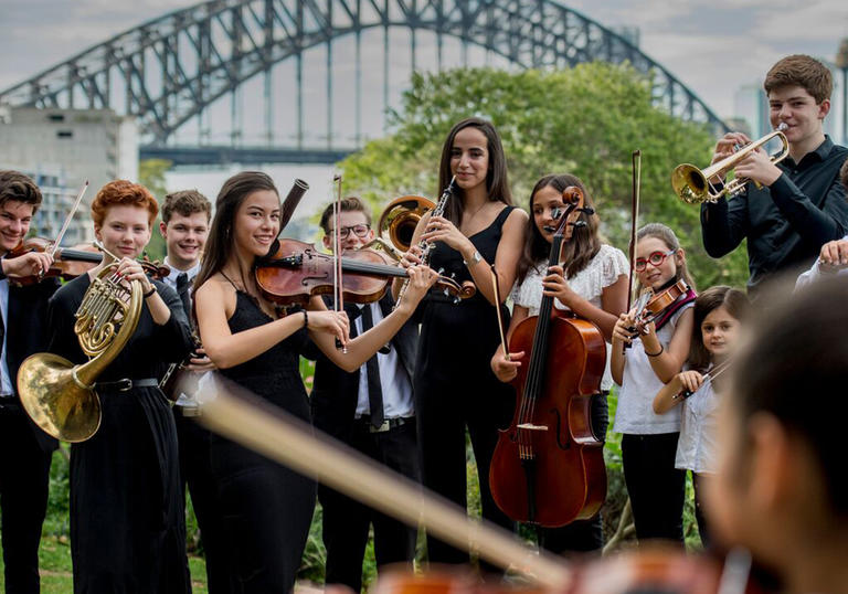 Players in the Sydney Youth Orchestra perform in front of Sydney Harbour Bridge