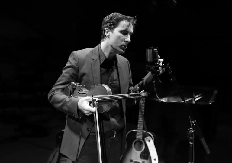 Andrew Bird holding his violin and singing into a microphone