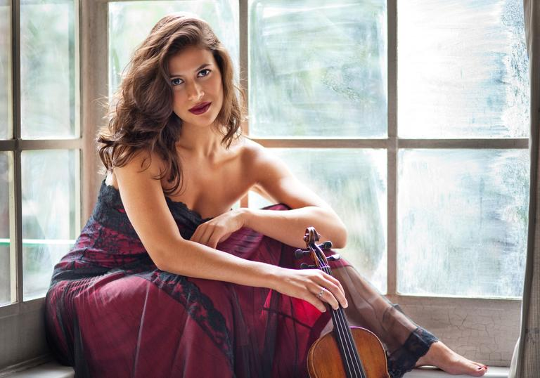 Elena Urioste sitting by window with violin
