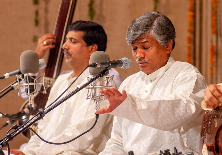 The Gundecha brothers wearing white and singing into microphones