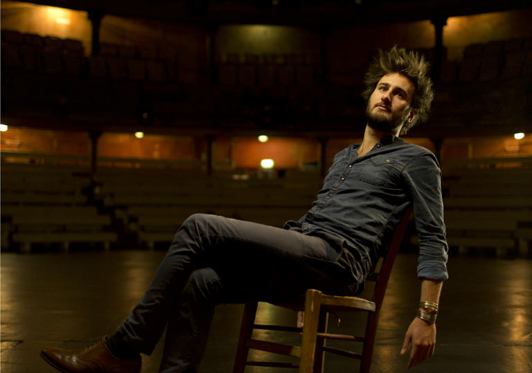 Jean Rondeauc leaning on chair on stage portrait