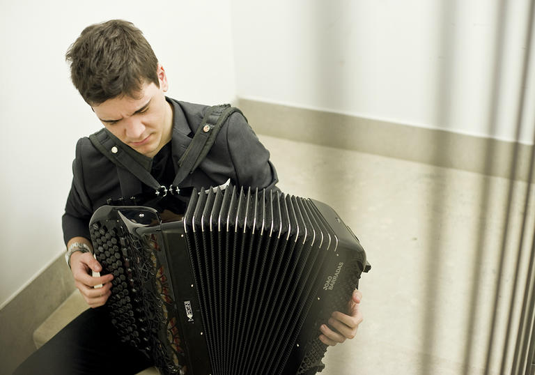 Joao Barradas playing accordion in stairwell