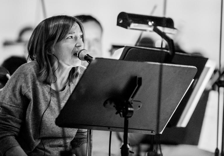Beth Gibbons singing into a microphone, with a music stand and headphones