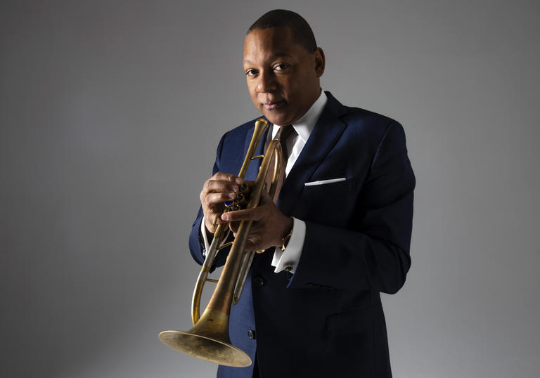 Wynton Marsalis wearing a suit, holdin his trumpet