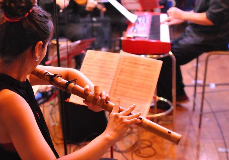 Hyelim Kim plays a wooden flute with other musicians in the background