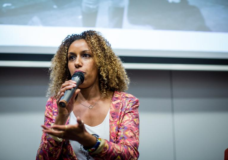 a woman stands with a microphone doing a talk