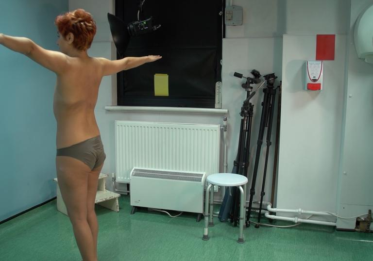 An undressed woman waiting to be looked over by a doctor in her hospital room.