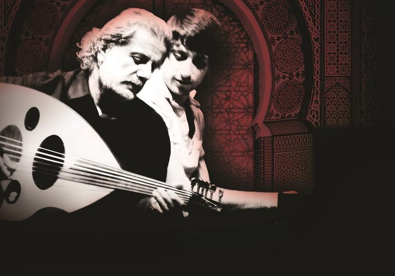 Marcel Khalifé playing his oud with Rami Khalifé behind him, looking over his shoulder as he plays piano