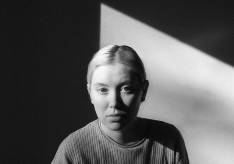 A black and white photo of Ellen Arkbro's head and shoulders. She is looking at the camera with a beam of light behind her.