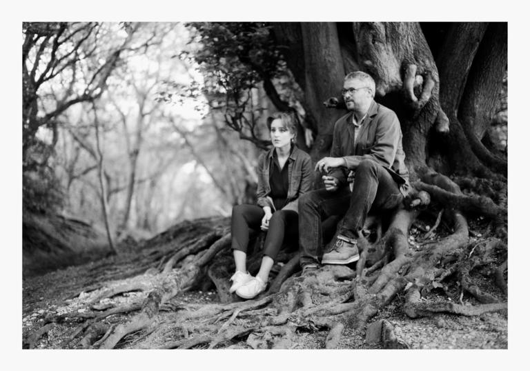 Hannah Peek and Will Burns sitting on the roots of a tree