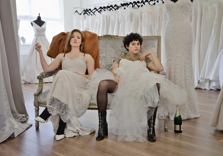 Holliday Granger and Alia Shawkat sitting in a wedding dress shop wearing wedding dresses pulled up to their knees