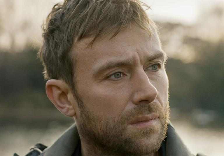 A headshot of Damon Albarn looking to the distance