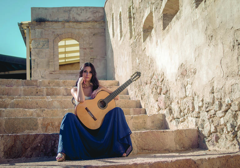 Guitarist Isabel Martínez sitting on stone steps in a sunny setting