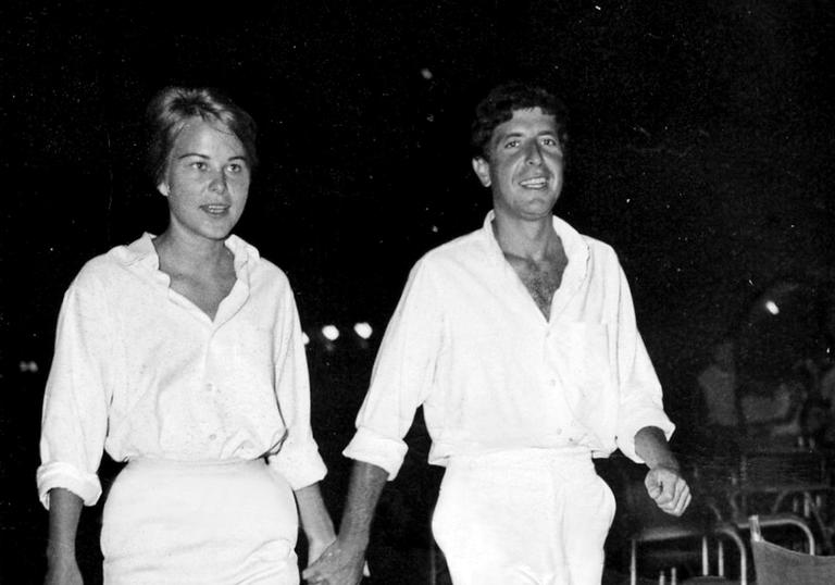 marianne and leonard walking together both wearing all white