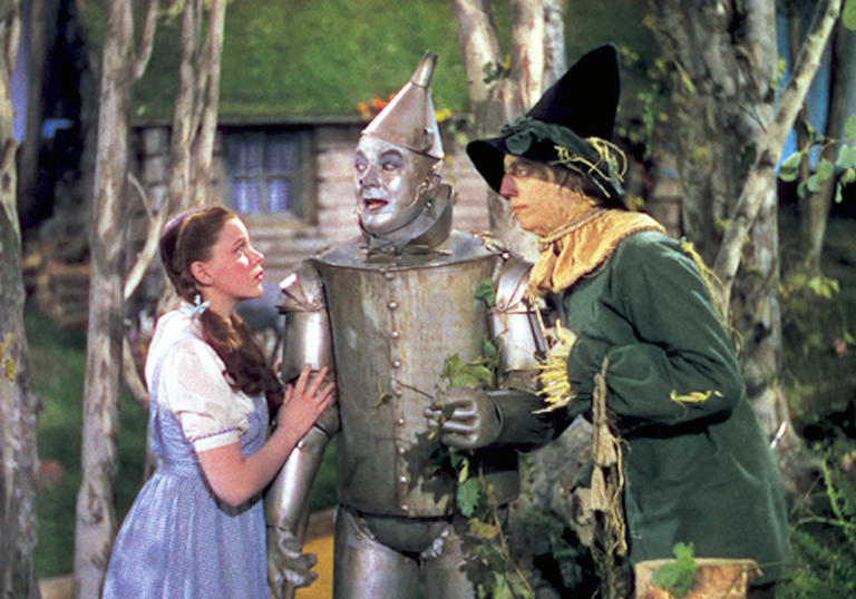 Dorothy, Tin Man and Scarecrow stand together in fear
