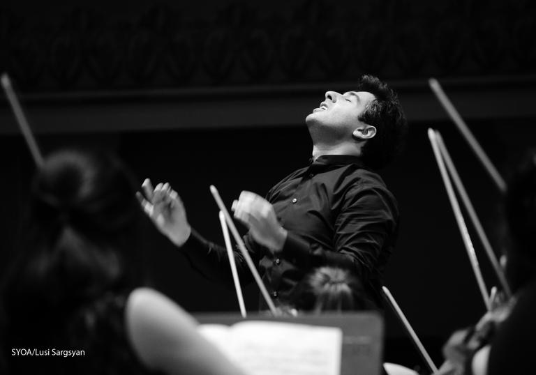 Sergey Smbatyan conducting surrounded by violin bows