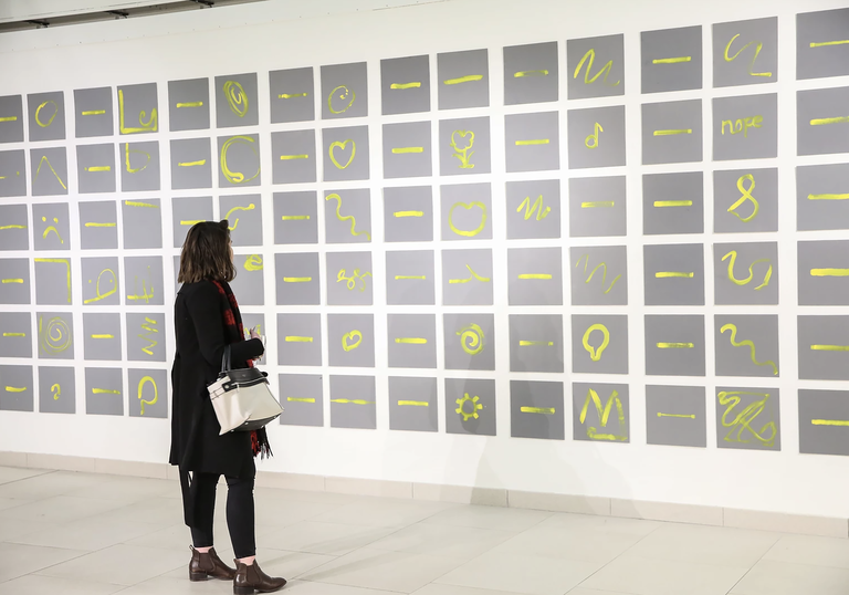An image of a woman looking at Charles Harrison's Single Yellow Lines: exploring single and expressive gestures through paint with people with and without dementia. 2017.