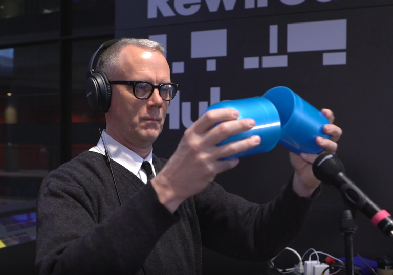 photo of a man with glasses holding a giant blue pill that is open in the middle