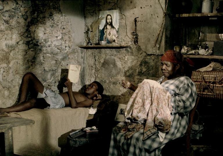 A young boy reads on a bed while his grandmother sews, in a bare-walled room in Martinique