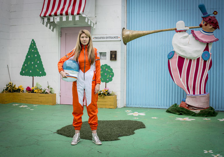 Beatie Wolfe wearing an orange space suit, with a colourful house behind her