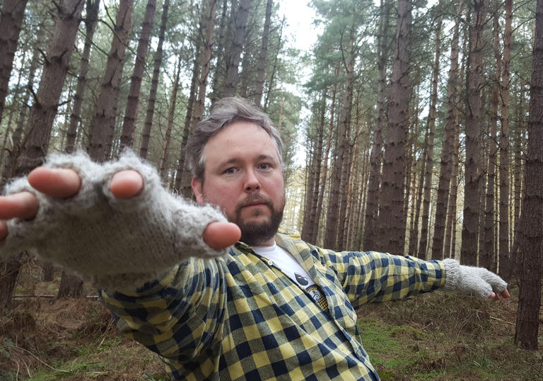 A man standing in the woods with an outstretched towards the camera