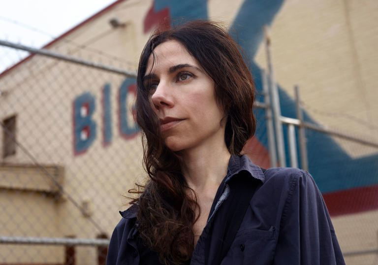 PJ Harvey in front of a cream building with a blue and red painted sign saying 'Big K'.