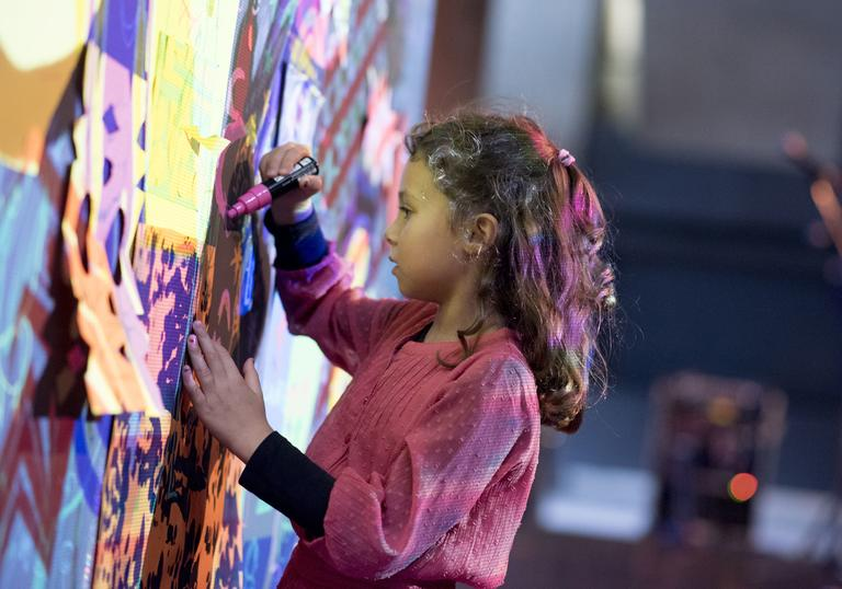 Girl drawing on a wall with projections