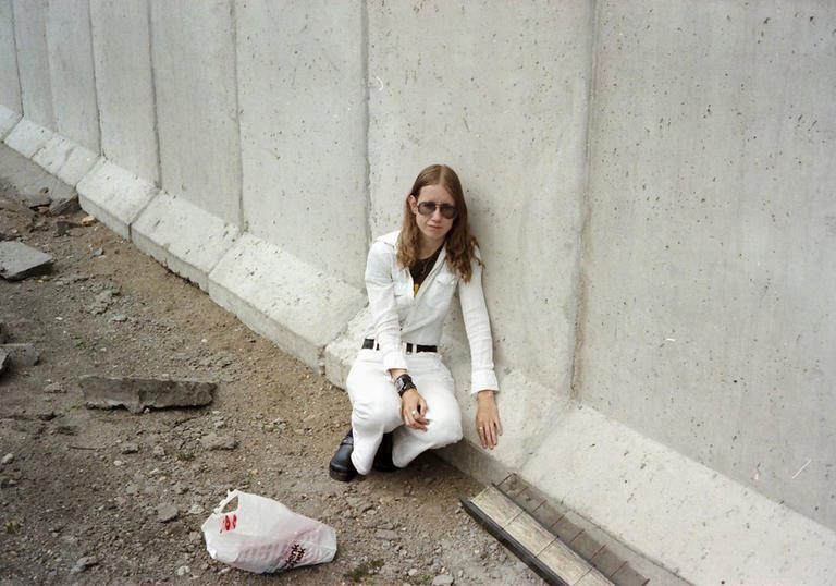 Woman dressed in white crouching next to the berlin wall