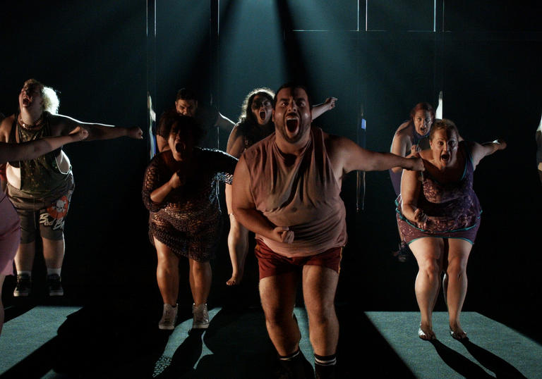 a dance troupe of dancers with larger bodies dances some choreography in a dark room