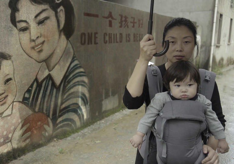A woman holding her baby in front of a chinese mural