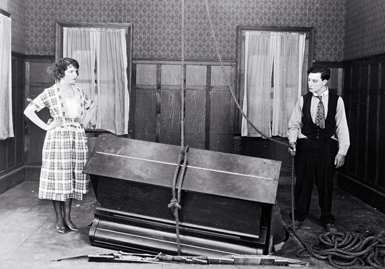 Buster Keaton and Sybil Seely stand in a room next to a piano which has crashed partially through the floor.