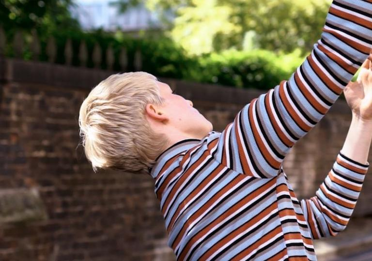 Blonde person in stripy polo neck dances down Leytonstone backstreet.