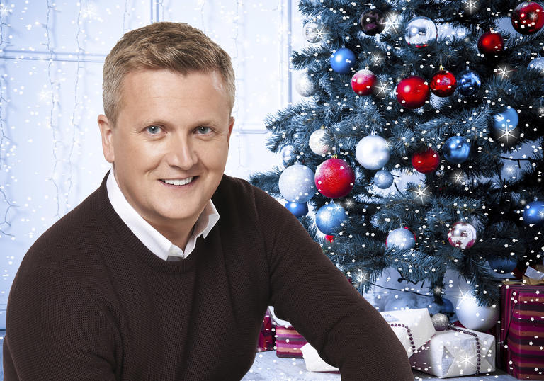 Aled Jones smiling in front of a Christmas tree