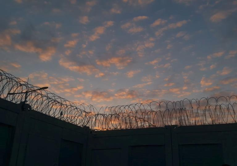a wall with barbed wire on it against a sunset sky