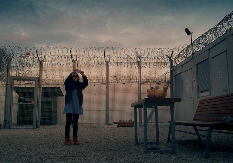 woman standing against the backdrop of a fence and sun setting sky